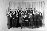Paul Whiteman and his Orchestra, gathered around piano