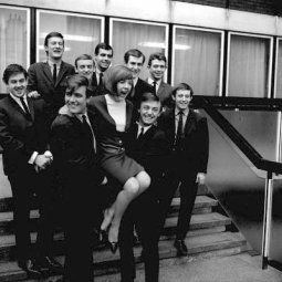 Cilla Black held by Billy J. Kramer and Gerry Marsden, with other members of the Dakotas and the Pacemakers