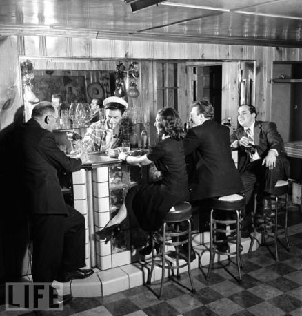 Frank Sinatra tends bar while smoking pipe