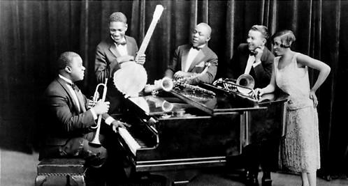 Louis Armstrong and his Hot Five, 1926. Left to right: Louis Armstrong at piano holding trumpet, Johnny St. Cyr with banjo, Johnny Dodds, Kid Ory, Lil Hardin Armstrong. American jazz band.