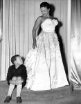 Hazel Scott modeling evening dress at Paris boutique, accompanied by son Skipper